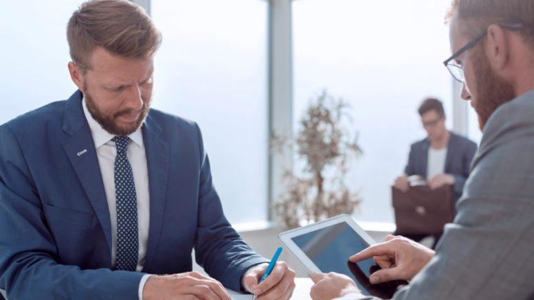 Hommes en costume et tablette numérique