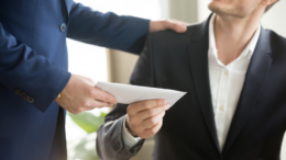 Un homme donnant une enveloppe à un autre homme au travail
