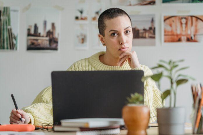 femme pull jaune en réflexion devant ordinateur