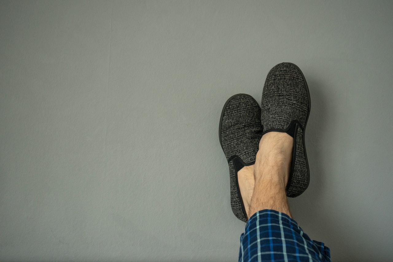 homme porte chaussons gris et pyjama tartan bleu et noir
