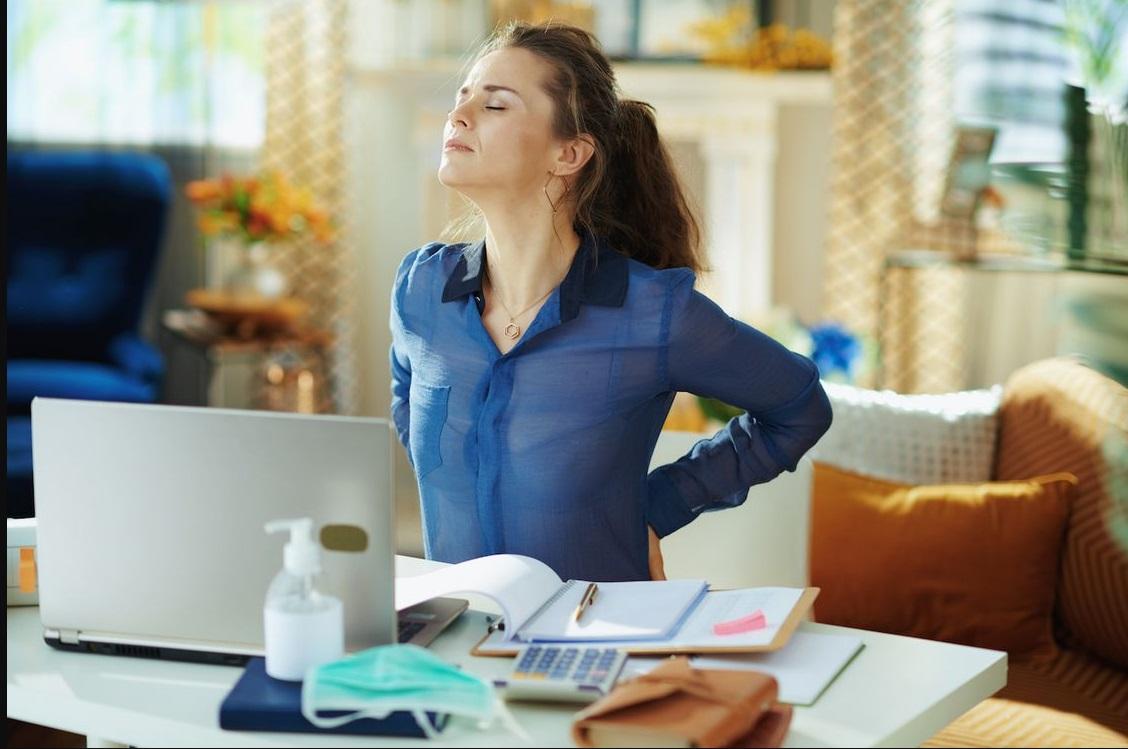 Télétravailleuse qui a mal au dos à son bureau