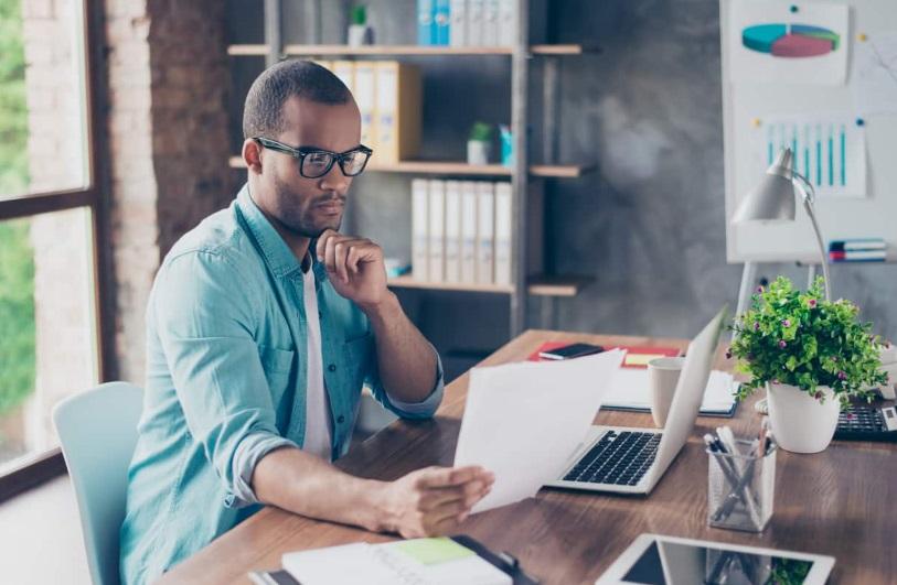 Homme avec ordinateur et documents
